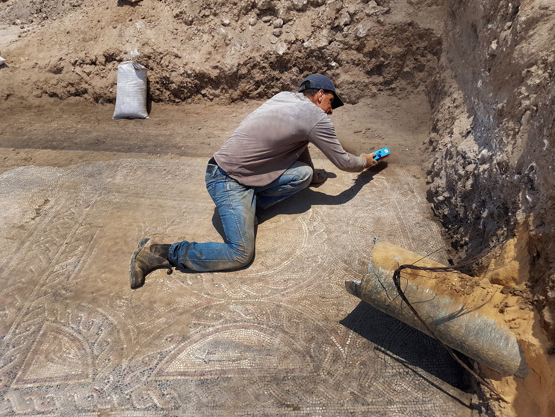 Painstakingly cleaning off the mosaic found in 1700-year-old house in Lod