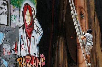 Artists painting a mural depicting Palestinian teen Ahed Tamimi.