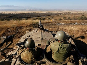Israeli soldiers watch the border with Syria near the Quneitra border crossing in the Golan Heights, July 3, 2013.
