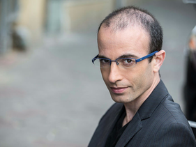 Prof. Noah Harari, 2015: Shown wearing blue-framed glasses, shaven. Some hair loss on top.