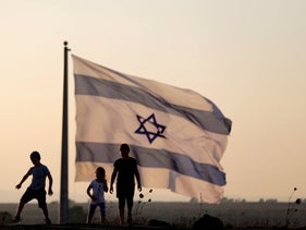 Israeli kids play next to an Israeli flag next to the Israeli-Syrian border on the Israeli-occupied Golan Heights, Israel. July 23, 2018