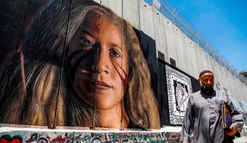 A Palestinian walks past a mural painted on Israel's controversial separation barrier in the West Bank city of Bethlehem on July 29, 2018, drawn by Italian artist Jorit Agoch, depicting Palestinian teenager Ahed Tamimi.