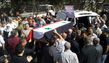 Syrian Druze carrying a coffin of one of the suicide attacks victims during a mass funeral in Sweida, July 26, 2018.