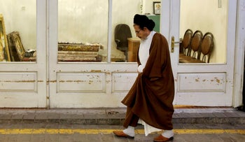 An Iranian cleric walks past the old main bazaar in Tehran, July 23, 2018.