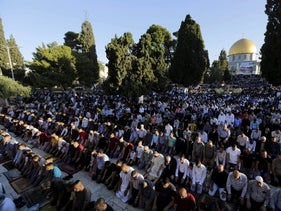 Palestinians pray in front of the Dome of the Rock shrine in Jerusalem on June 15, 2018.