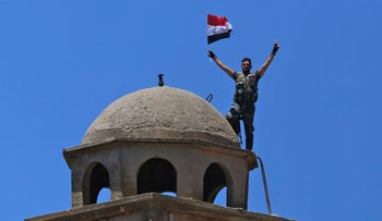 A Syrian soldier waves the national flag atop the Greek Orthodox Church of St. George in the town of Quneitra in the Syrian Golan Heights on July 27, 2018.