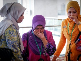 Sarah Nor, center, the mother of Norliakmar Hamid, a passenger on the missing Malaysia Airlines Flight 370, cries after she listened to an investigation report on missing Flight 370, in Putrajaya, July 30, 2018.