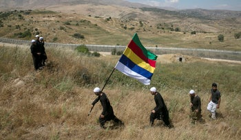 Members of the Druze community walk next to the border fence between Syria and the Israeli-occupied Golan Heights, near the Druze village of Majdal Shams, as others watch the fighting in Syria's ongoing civil war.