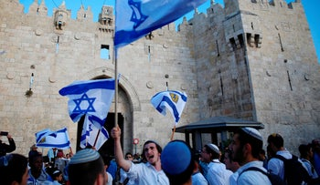 Israelis wave national flags outside the Old City's Damascus Gate, in Jerusalem, May 13, 2018