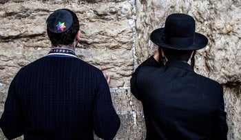 A member of the American LGBTQ community praying next to an ultra-Orthodox man at the Western Wall in Jerusalem's Old City, May 2016.
