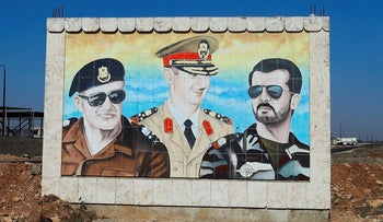 Mural depicting the Syrian President Bashar Assad (C), his father late Syrian President Hafez Assad (L), and his dead brother Bassel Assad, outside a military base in Homs, Syria. July 17, 2018