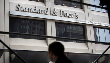 A pedestrian passes in front of Standard & Poor's headquarters in New York, U.S., on Tuesday, Feb. 5, 2013