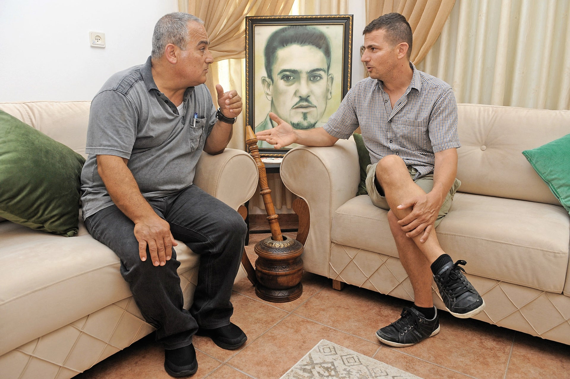 """Jamal Barakat, left, with director Ramy Katz (an image of Salim is behind them). """"In the end,"""" says Katz, """"the testimonies supported the version that he was shot by a civilian."""""""