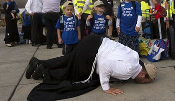 A newly-arrived Jewish immigrant coming from North America with his family kisses the tarmac upon their arrival at the Ben Gurion International Airport near Tel Aviv on July 23, 2013.