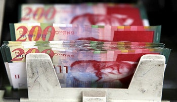 Israeli two hundred shekel bank notes sit on a counting machine in Jerusalem, Israel.