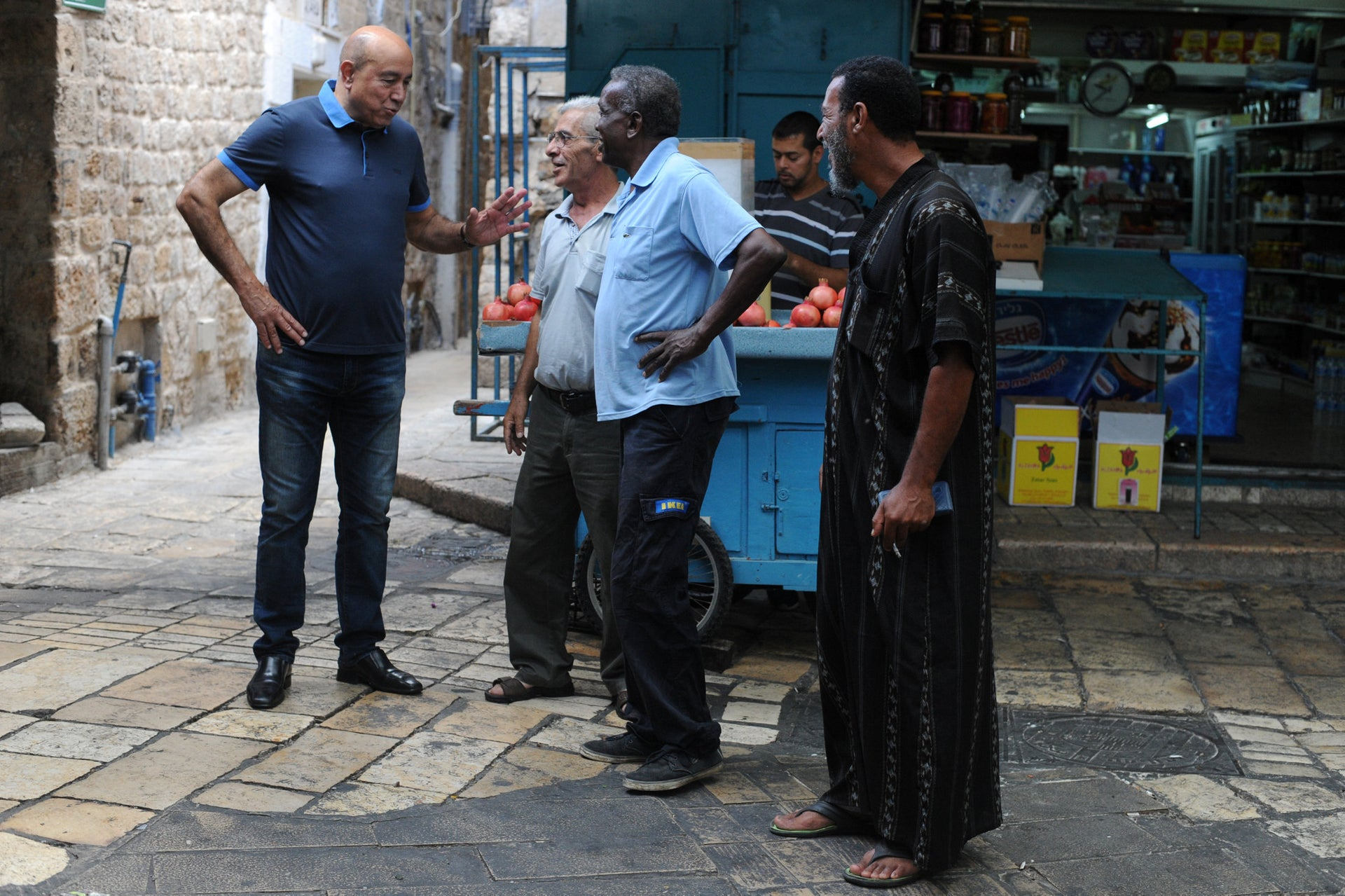 Former Knesset Member Zouheir Bahloul talks to people at the Acre market.