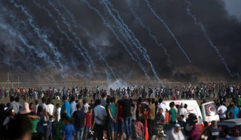 Teargas canisters fired by Israeli troops fall over Palestinians during a protest at the Gaza Strip's border with Israel, July 13, 2018.