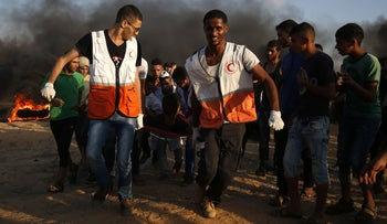 Palestinian protesters and rescuers carry a wounded protester during a demonstration at the Israel-Gaza border, August 3, 2018.