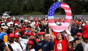 A man holds up a large 'Q' sign while awaiting the arrival of U.S. President Donald Trump at a rally at the Mohegan Sun Arena, Wilkes Barre, Pennsylvania, August 01, 2018.