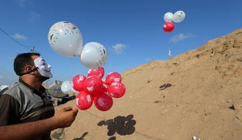 Palestinians fly balloons loaded with flammable material to be thrown at the Israeli side, near the Israel-Gaza border in the central Gaza Strip, June 4, 2018