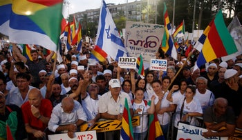 Protesters wave Druze and Israeli flags and banners at a rally against the nation-state law, Tel Aviv, Israel, August 4, 2018.