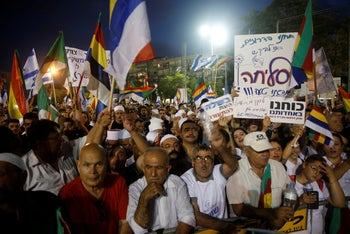 Members of the Druze community holding signs at a protest against the nation-state law in Tel Aviv, August 4, 2018.