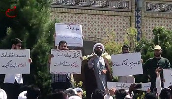 In this video grab made from a video by Nasim News Agency, a cleric speaks to a crowd of protesters demonstrating in Mashhad, in the Khorasan Razavi province, on August 3, 2018.