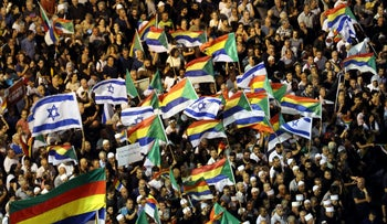 Israelis from the Druze minority together with others Hold Israeli national flags and Druze's flags as they take part in a rally to protest against Jewish nation-state law in Rabin square in Tel Aviv, Israel, August 4, 2018