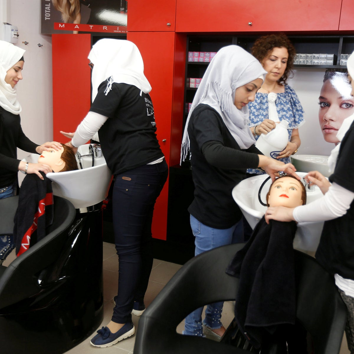 Women practice on hair mannequins at a training salon in Bar Elias town, in the Bekaa valley, Lebanon July 25, 2018. Picture taken July 25, 2018.
