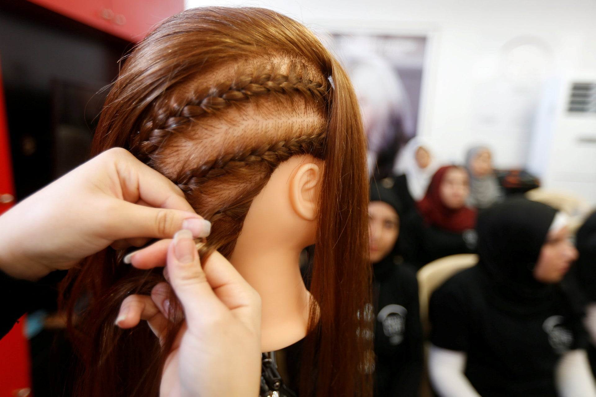 A woman practices on hair mannequins at a training salon in Bar Elias town, in the Bekaa valley, Lebanon July 25, 2018.