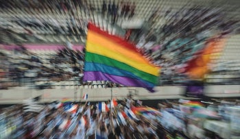 This picture taken with long time exposure shows participants of the French team holding a rainbow flag as they march onto the field during the opening ceremony of the 2018 Gay Games edition at the Jean Bouin Stadium in Paris on August 4, 2018
