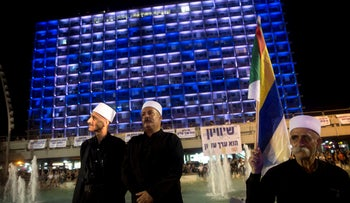 The Israeli flag is projected onto Tel Aviv's city hall during a protest against the nation-state law led by the Druze community, August 4, 2018.