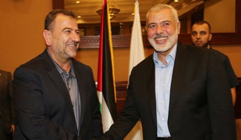Hamas senior Ismail Haniyeh shakes hands with his deputy Saleh Arouri upon his arrival in Gaza from Cairo, Egypt, in Gaza City, August 2, 2018.
