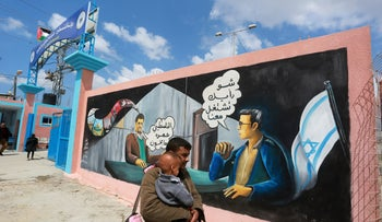 Palestinians walks in front of a painting at Erez Crossing, North Gaza Strip, on March 21, 2016