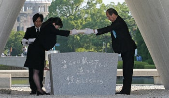 Hiroshima Mayor Kazumi Matsui (R) offers a new list of A-bomb dead, including individuals who died since last year's anniversary from the side effects of radiation, during the 73rd anniversary memorial service for the atomic bomb victims at the Peace Memorial Park in Hiroshima on August 6, 2018