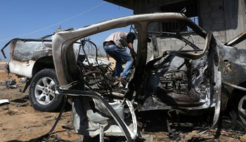 A Palestinian man inspecting a damaged car after an Israeli strike on the northern Gaza Strip, August 5, 2018.