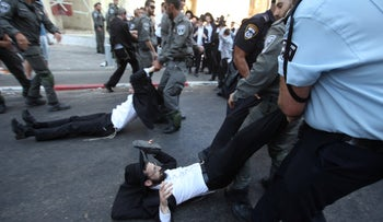 Policemen drag demonstrators who blocked the road in Bnei Brak during a protest against IDF conscription, on August 6, 2018.
