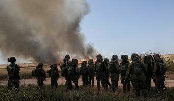 Israeli soldiers watch a wheat field that caught fire next to kibbutz Nahal Oz along the Israel-Gaza border, Monday, May 14, 2018.