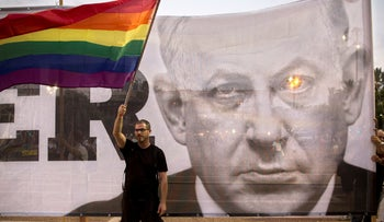 An Israeli waves a flag in front of a banner showing Israeli Prime Minister Benjamin Netanyahu during a rally to protest against inequality for the LGBT community in Tel Aviv, Israel, Sunday, July 22, 2018. Thousands of Israeli LGBT advocates and their supporters went on strike across the country Sunday, protesting the exclusion of gay men from a recently passed surrogacy law. (AP Photo/Sebastian Scheiner)