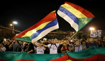 A man waves Druze flags as Israelis from the Druze minority, together with others, take part in a rally to protest against Jewish nation-state law in Rabin square in Tel Aviv, Israel, August 4, 2018.