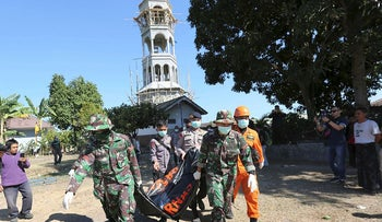 Rescuers carry a body of an earthquake victim recovered from the collapsed Jabal Nur Mosque in North Lombok, Indonesia, Tuesday, Aug. 7, 2018