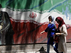 Iranians walking by the a mural painting of Ayatollah Khomeini on the wall of the former U.S. embassy in the Iranian capital of Tehran, August 7, 2018.