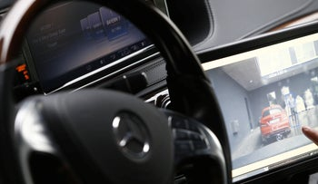 A focus point box highlighting a pedestrian on a monitor inside a Mercedes-Benz during the Daimler AG Tech Day demonstration.