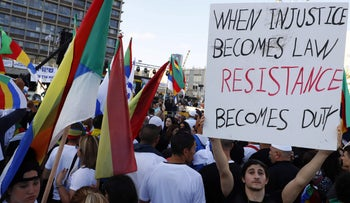 A man holds a banner during a rally to protest against the 'Jewish Nation-State Law' in Tel Aviv, Israel on August 4, 2018