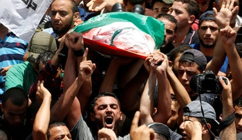 Palestinian mourners shouting slogans as they carry the body of a Hamas militant who was killed in an Israeli tank shelling, during his funeral on August 7, 2018.