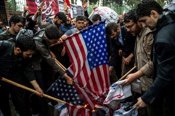 Iranians preparing to burn American flags during an anti-U.S. demonstration outside the former U.S. embassy in Tehran.