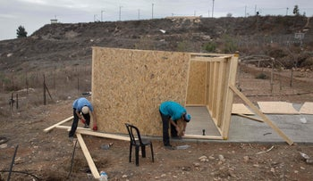 Israeli settler youths build a new wooden structure in the settlement outpost of Amona, which was established in 1997, in the Israeli-occupied West Bank on November 29, 2016.