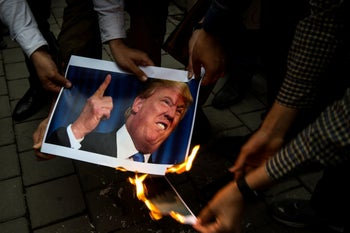 Iranians burn a photograph of U.S. President Donald Trump during an anti-U.S. demonstration outside the former U.S. embassy headquarters in Tehran, Iran, on Wednesday, May 9, 2018.