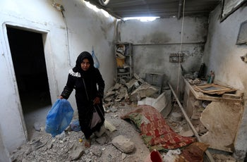 A woman inspects a damaged house where a Palestinian woman and her 18-month old child were killed, in the Gaza Strip, August 9, 2018.