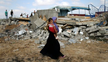 A Palestinian woman carries a girl as she walks past the site of an Israeli airstrike, Khan Younis, southern Gaza Strip, August 9, 2018.